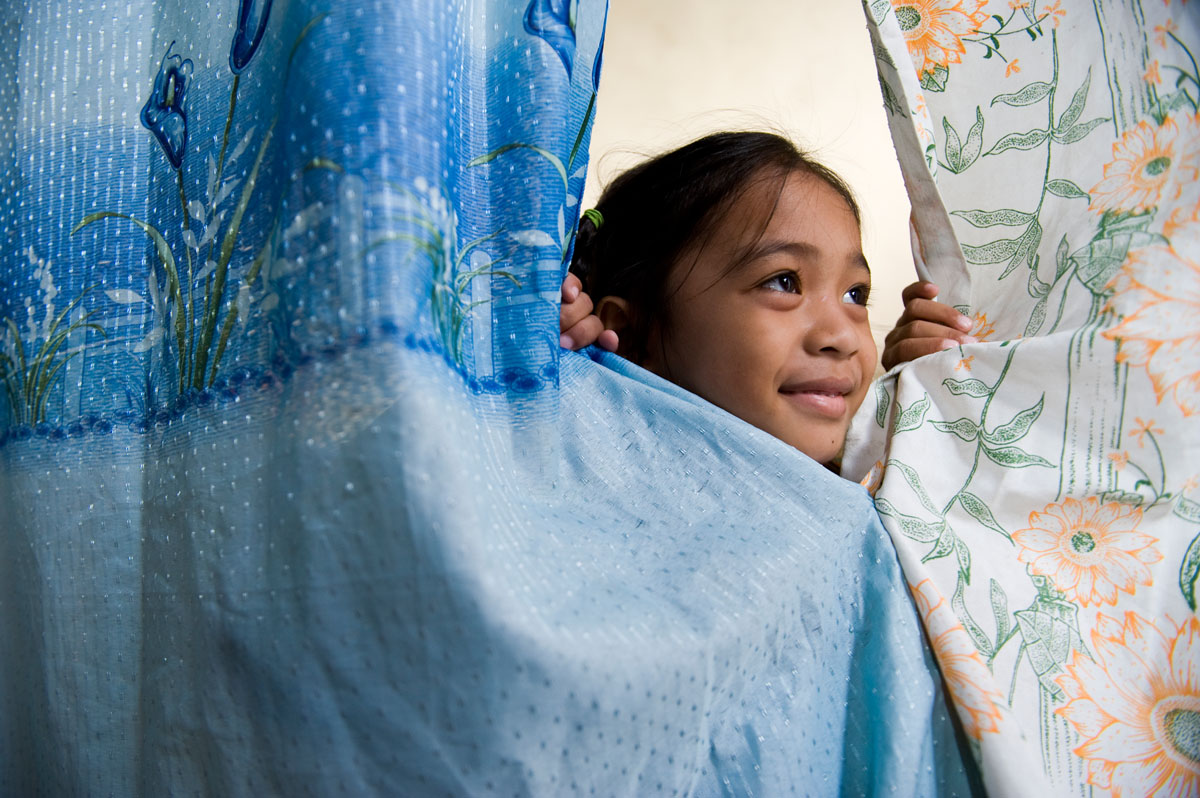 Angelica Martinez peers through the sheets that separate her family from the neighbors at the Muntinlupa elementary school, where 357 displaced families live after typhoons destroyed their homes.© Habitat for Humanity International/Ezra Millstein