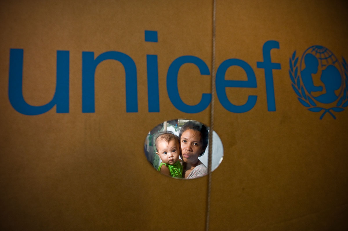 Sharon Bon and her 5 month-old daughter Ina look in a makeshift mirror, in the middle of the Muntinlupa elementary school.  357 displaced families live in the school after typhoons destroyed their homes.© Habitat for Humanity International/Ezra Millstein