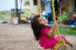 Four year-old Racquel Aparenga plays on a swing in front of her family's Habitat home in the Brisas del Sur community.   © Habitat for Humanity International/Ezra Millstein