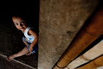 One year-old Catherine Mellssa Vasquez plans on the floor near the door of her family's small home.  Habitat volunteers helped to renovate the kitchen, inproving ventilation and ensuring better respiratory health for Catherine and her family.© Habitat for Humanity International/Ezra Millstein