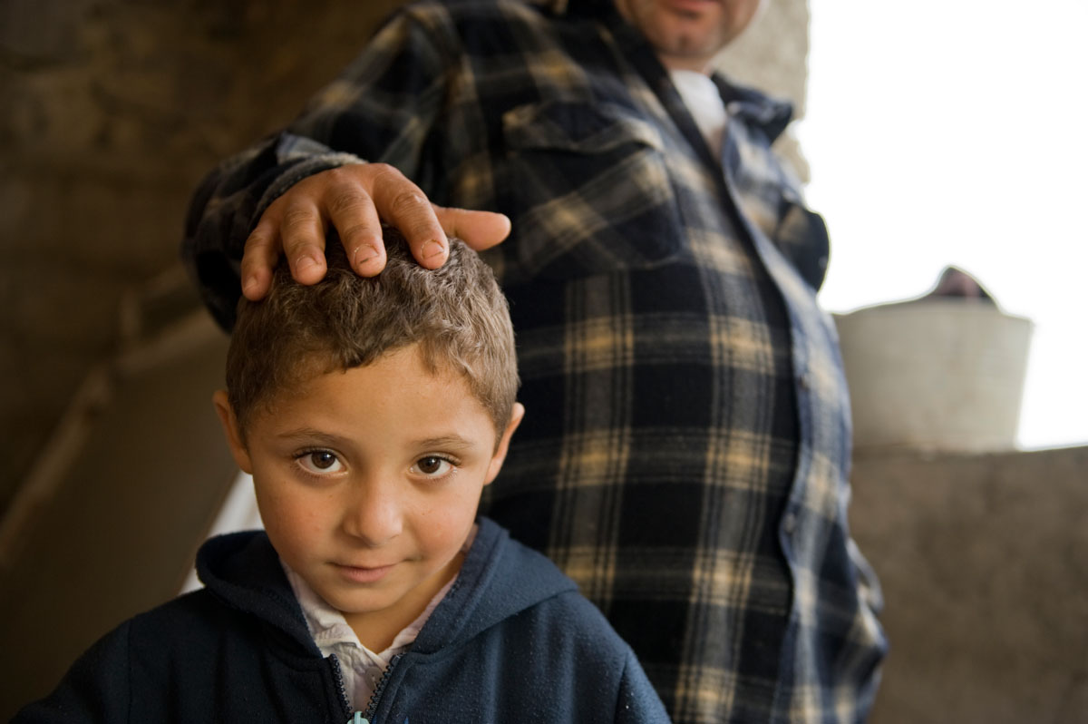 Six year-old Dezika Rac stands next to his father Pater.  Their home is in a Roma community in Hodejov; it is being rehabilitated thanks to a loan from Habitat for Humanity Slovakia.© Habitat for Humanity International/Ezra MIllstein