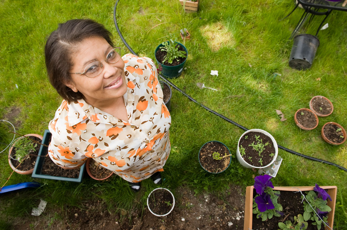 Angelina Lopez tends her garden in the front yard of her Habitat home.  She and her daughter Janai moved into the house in 2005.   © Habitat for Humanity International/Ezra Millstein