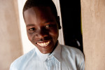 Gilbert Byensi is the 13-year-old nephew of Ayediida Mbagaineki.  Mbagaineki took Gilbert in because his mother had died, and his stepmother was not treating him well.  Mbagaineki is a 56-year-old widow who has also taken in four grandchildren; they live in her new house, which  she completed with the help of two loans from Habitat for Humanity Uganda.  Her 26-year-old daughter, Asaba, also lives with her.  Theyused to live in a deteriorating mud hut; now they have a spacious home, and they use the old mud huts on the property as shelter for their goats and chickens. © Habitat for Humanity International/Ezra Millstein