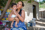 Ana Maria holds her 3 month-old daughter Fabiola. She was pregnant with Fabiola when the family received a cash disbursement from Mercy Corps, and the money allowed her to get medical care for the birth. They say they would have had no way to go to the hospital without the assistance. The family also purchased essential household items for their shelter. Ana Maria and her husband Jose Eduardo Monasterio Castañeda withstood the crisis in Venezuela for as long as they could, but when their situation grew so desperate that they were drinking glasses of water for dinner, they made the painful decision to leave their home and seek survival in Colombia. More than 1 million Venezuelans have fled to Colombia, fleeing economic, governmental and social collapse that has plunged the majority of the population into poverty, joblessness and near starvation. Many, like Jose and Ana Maria, are funneling into communities that already struggled with poverty and lack of opportunity, and resources are at a breaking point. Jose and Ana Maria now live with their five children in a small room at the back of another house along a busy street in Riohacha. They earn money selling small goods and mobile phone minutes on the street where they live, but the income is not enough, and Jose worries about his children's future. Mercy Corps is distributing emergency cash to help vulnerable Venezuelans in Colombia meet their urgent needs, including food, medicine and shelter.