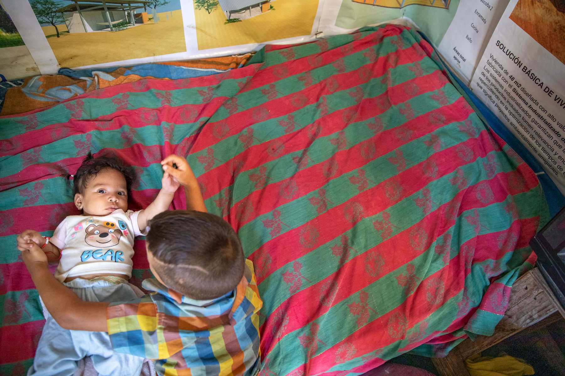 Eduard, 6, lies on a bed with his 3 month-old sister Fabiola in his family's shack. They live with their three siblings, and parents Jose Eduardo Monasterio Castañeda and Ana Maria. Jose and Ana Maria withstood the crisis in Venezuela for as long as they could, but when their situation grew so desperate that they were drinking glasses of water for dinner, they made the painful decision to leave their home and seek survival in Colombia. More than 1 million Venezuelans have fled to Colombia, fleeing economic, governmental and social collapse that has plunged the majority of the population into poverty, joblessness and near starvation. Many, like Jose and Ana Maria, are funneling into communities that already struggled with poverty and lack of opportunity, and resources are at a breaking point. Jose and Ana Maria now live with their five children in a small room at the back of another house along a busy street in Riohacha. They earn money selling small goods and mobile phone minutes on the street where they live, but the income is not enough and Jose worries about his children's future. Mercy Corps is distributing emergency cash to help vulnerable Venezuelans in Colombia meet their urgent needs, including food, medicine and shelter. Ana Maria was pregnant with 3-month-old Fabiola when the family received their cash disbursement from Mercy Corps, and the money allowed her to get medical care for the birth. They say they would have had no way to go to the hospital without the assistance. The family also purchased essential household items for their shelter.