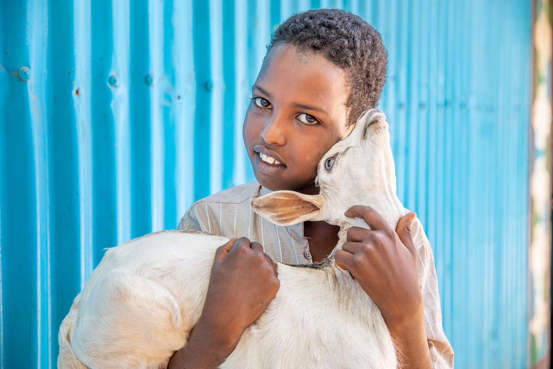 "Farhan, 12, holds a goat in front of his family's house. His mother Safiya, 45, is a community leader in Hartasheik, Ethiopia. Mercy Corps trained her and several others in her community to help change dangerous traditional behaviors about women's health and natural resource management. Now the community is connected to health services and protecting the vital land that provides for them.""Women should take leadership roles, and I feel comfortable doing it,"" she says. ""It's obvious that women are taking the lead in Ethiopia. The leadership is there and women are taking hold of it."""