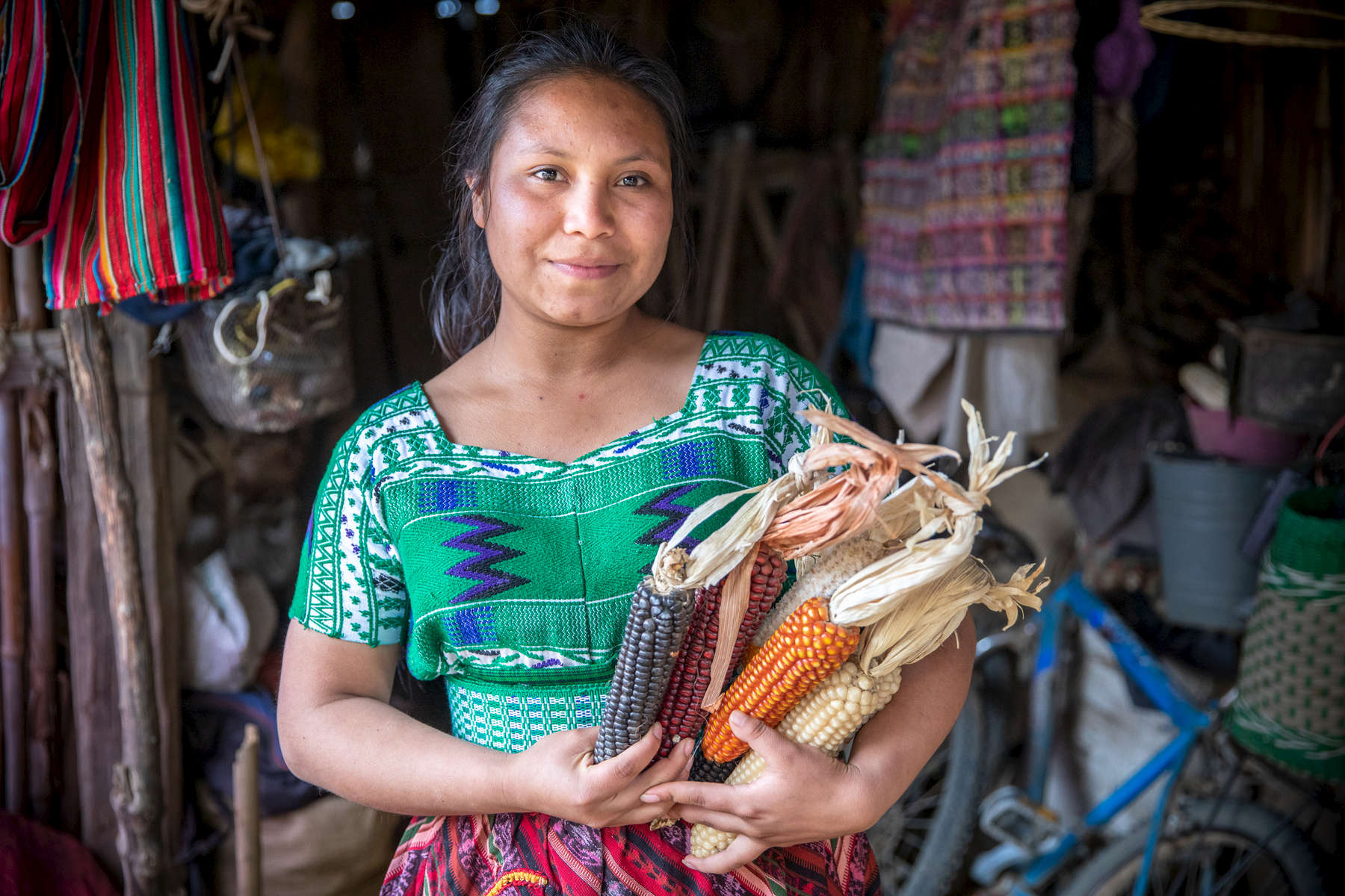 Olga Lucretia Matzar, 18, holds dried corn in front of her family's home. We first met Olga in 2017 when she was a participant of Mercy Corps' AgriJoven program, which works to prevent youth migration out of Guatemala's Western Highlands. At that time, she had dropped out of school so she could work and help support her family, and had thought about migrating to the city for better opportunities.A year and a half later, Olga is more optimistic than ever that she can stay in her community and build a life. Through the program she learned farming techniques to help her parents improve their crops and triple the land they farm, and saved enough through her savings and loan group to return to school. She is now studying to be a teacher, and she wants to be a role model for other young people so they see opportunity in their community and choose not to migrate.  Much of Guatemala's migration occurs out the Western Highlands, an agricultural region characterized by underdevelopment, poverty and a lack of opportunity. AgriJoven provides youth with agricultural training and savings and loan groups, which offer them a chance to see a future in agriculture or invest in other ventures without having to leave home.