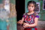 """Heidy, 9, weaves on front of her family's home in a small community in Guatemala's Western Highlands. It is an agricultural region characterized by underdevelopment, malnutrition, poverty and a lack of opportunity. Her grandmother, Maria de León Santiago, recently started saving for the first time ever through the """"Communities Leading Development"""" program, which is implemented by local partners with technical support from Mercy Corps. The program aims to improve quality of life for families in 200 communities in the Western Highlands, in part by installing community savings and loans groups to build financial stability. Maria is the president of her savings and loan group, and she says she is focused solely on saving right now, so she can give her family a better life than she had growing up."""