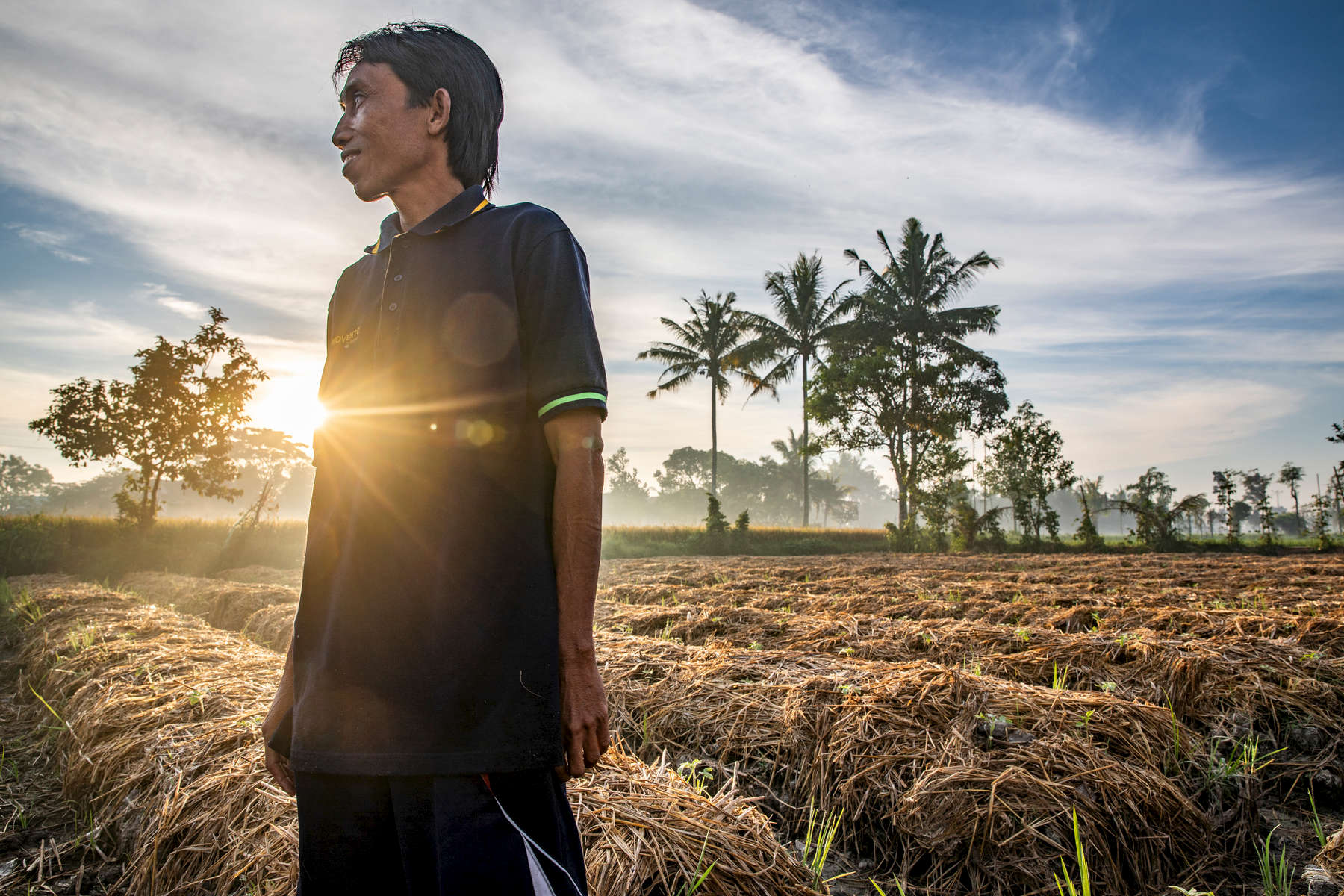 """Pak Sahwil, 42,  stands in his vegetable fields. He is a rice farmer on Lombok in eastern Indonesia. Mercy Corps is helping him and the 60 other farmers in his farmers group learn how to grow stronger, heartier crops in the face of worsening drought.Lombok is extremely vulnerable to climate change, with shorter rainy seasons and longer dry seasons that put precious harvests at risk.A lifelong farmer on Lombok—and the son of rice farmers—Pak Sahwil can recall the dry seasons as far back as 15 years. As he gets older, he worries about longer droughts causing harvest failure. """"Sometimes, climate change causes failure. What I feel the most is a long dry season,"""" he says.On Lombok, the dry season is now regularly starting a month earlier and lasting a month longer, leading to dangerous water shortages for farmers. """"I'm very worried. Not just for next year, but even for this year. Accessing water is becoming difficult,"""" Pak Sahwil says.Mercy Corps has helped Pak Sahwil and the farmers group he mentors endure drought with better farming practices and business training. """"Our objective as farmers is to increase our production. Because the Mercy Corps mission is the same as ours, we cooperate. This is a good opportunity, in my opinion,"""" he says.Mercy Corps trains farmers like Pak Sahwil to organize local farmers groups where farmers work together and support each other. They also learn to start agribusinesses to supplement their income.Pak Sahwil also works for the governmental agriculture agency. When he saw how Mercy Corps was improving local farmers, he extended the partnership to other districts. """"Because Mercy Corps is successful with my group, I share the knowledge with the group in this village,"""" he says."""