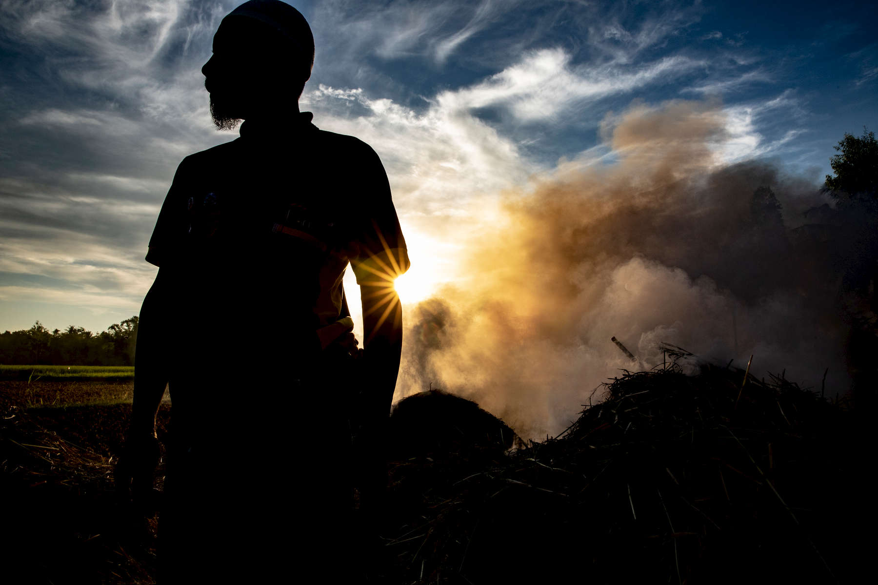 Muhammad Nuh Gazali, 39, stands among smoke from burning rice chaff at the end of a day of harvesting.  Indonesia's farmers help feed 249 million people. But climate change is threatening their way of life with longer droughts and erratic rainy seasons that threaten the harvests they rely on.In Indonesia, climate change is an ever-present reality. The average temperature in Lombok has risen nearly three degrees since 1948, and is predicted to rise another two degrees by 2060—a dangerous reality for farmers who depend on the climate to survive.Droughts in Lombok can last for months and threaten the precious harvests that farmers rely on. Rainfall in Indonesia has decreased by 3 percent since 1900 and climate change is expected to get worse over the next 50 years.Lombok is predicted to experience a massive decline in water reserves by 2030, threatening the island's farmers and the people who rely on their harvests to survive.In just 20 years, the risk of crop failure due to climate change is expected to double on Lombok.In one of the world's most vulnerable places to climate change, Mercy Corps has helped more than 6,000 farmers increase their yields and the incomes that support their families. Over the next three years, Mercy Corps aims to help 20,000 rice farmers in Indonesia increase their incomes by at least 28 percent.Mercy Corps teaches rice farmers how to select the best seeds to plant and the best time of year to plant them, as well as how to detect and treat disease.