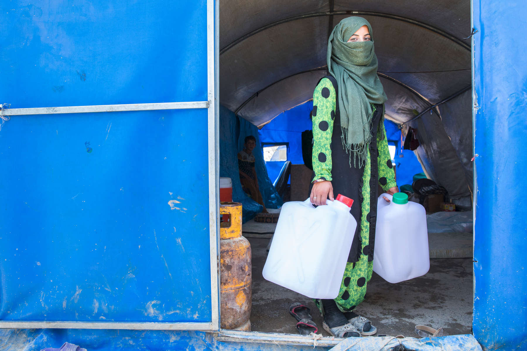 Freeal Jummah, 15, holds two jerrycans that her family received as part of a Mercy Corps NFI distribution. Hers is one of 400 families that received NFI kits from Mercy Corps on this day; the kit included 6 blankets, 2 jerrycans, a tarp and a rope.Before the crisis, her family farmed for a living. They fled the fighting in Shirqat, south of Mosul, and have been in IDP camps since January. Freeal and her siblings wait in line for water twice a day for up to an hour. Her mother, Hela Salama Jummah, said {quote}This is my country, my birthplace. I would hope to be able to go home.""