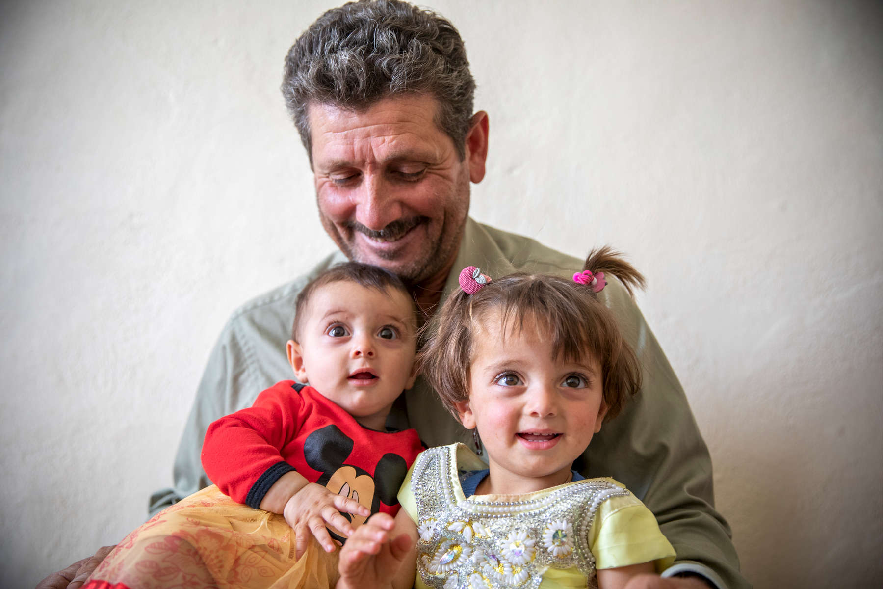 "Ahmad, 51, holds his granddaughters Zinab, 2, and Bilasan, 6 months. They are Syrian refugees living in an informal tent settlement. They fled Syria in 2012 when a bomb destroyed their home. Since then, they have lived in a tent community with 23 other families, where Ahmad built a schoolhouse that teaches more than 40 Syrian kids.Ahmad was a farmer back in Syria, but when he saw how none of the children in this community could read or write, he decided to be their teacher. The walls of his classroom are covered in posters teaching English, Arabic, science and math, while the ceiling is decorated with recycled materials the children gathered. ""I try to put hope for the children here. So I'm proud of what I did,"" he says.More than 700,000 Syrian refugee children are out of school. Ahmad built this classroom so that when the time comes for the kids in his community to return to Syria, they'll be ready to pick up their education again. ""I built everything here by myself,"" he says. ""I started this to teach children here, because if I didn't, they would take their own direction in their life and do the wrong thing, like drugs or going to the streets. Children in this generation are our future. Because of that, I started this school.""Ahmad's school teaches children ranging from ages 5 to 13. They meet from 8 a.m. to noon, six days a week. At first there were no chairs, and the students sat on rocks in the sand. The community pulled together to help buy carpet, stools, and school materials. ""It's a benefit for everyone here,"" he says.Ahmad uses Khabrona, a digital platform built by Mercy Corps and Cisco to help refugees access critical services through their cell phones. Once he used the app, he was able to get documentation for his son to live legally in the country. ""I felt relief,"" he says. ""I felt like I was legal because I could go back and forth and my child could go back and forth …  This program really helped a lot of families."" Ahmad lives about 13 miles from the Syrian border—close enough to hear the sound of airstrikes in the distance. The sound is a reminder of the life he used to have and the struggles he's endured for his family's safety. ""I used to own a farm, now I'm working for a farmer. I used to make people work for me and respect them, now I'm working for someone who doesn't respect me,"" he says. ""It was really hard. We have a lot of depression.""Ahmad has a close relationship with the kids in his school, who call him Teacher or Uncle. When the kids hear the airstrikes, they often come to him to ask him to explain it. ""Most of the children actually didn't live this, so at first they didn't know,"" he says. ""They thought it was fireworks. But after they go back to their parents and start to see the news, they come back to me and ask me about it, ""We saw the news and people died and everything."" I tried to make the picture better, but you can't. I tried, but it will stay a black picture because someone died."""