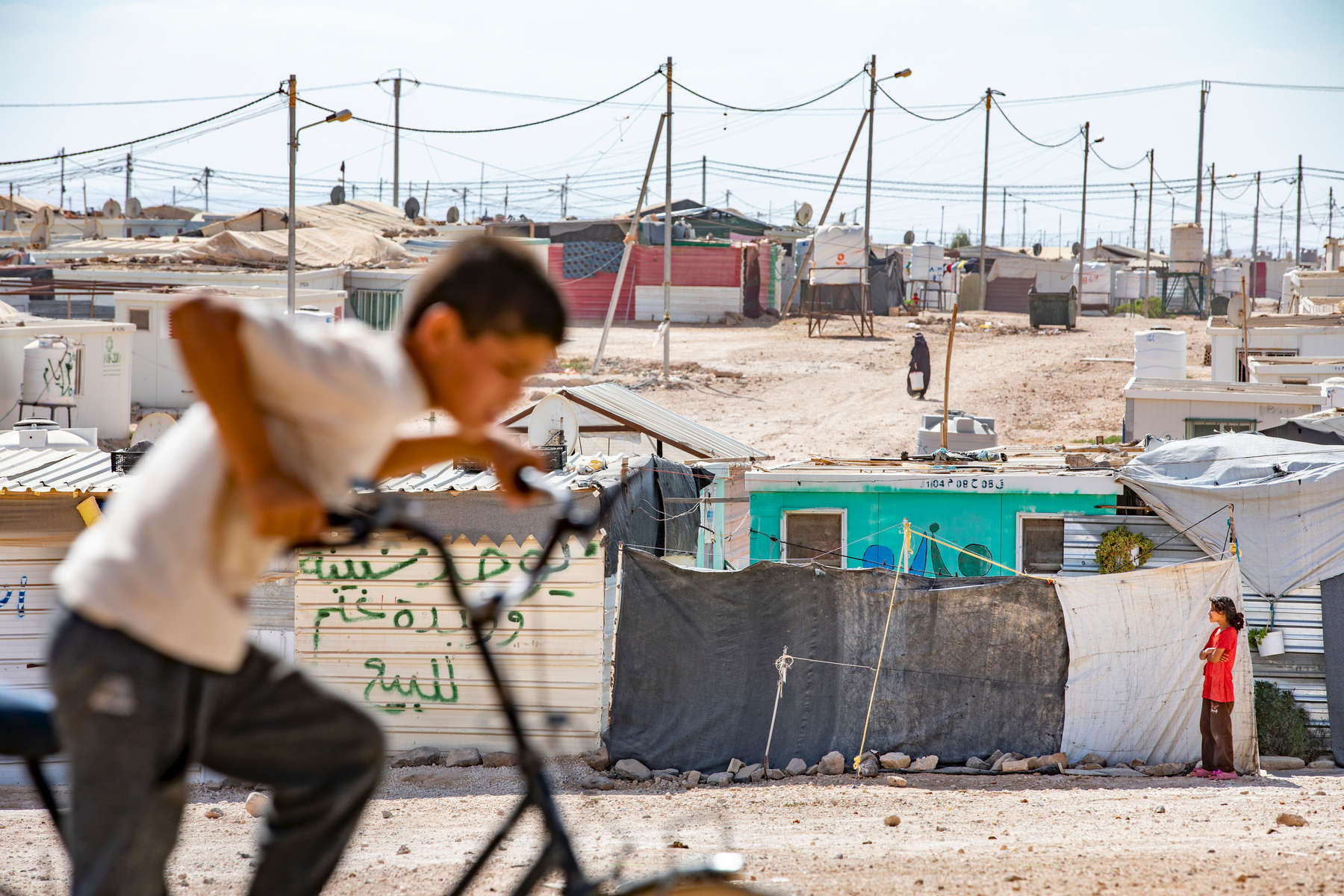 Children play on the outskirts of Zaatari refugee camp. Mercy Corps operates a safe space inside Zaatari, where Syrian refugees learn about healthy parenting strategies and make traditional Syrian crafts that help them stay connected to their home. The space, which features a playground, garden, soccer field, and classrooms, gives adults and children a safe place to stay in the middle of the dusty camp.