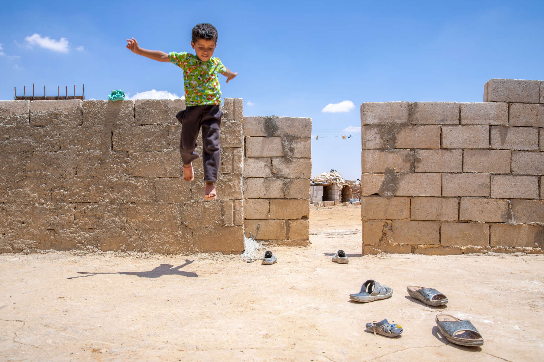 """Ahmad, 10, a Syrian refugee, plays on a wall next to his neighbor's family's goat pen. The neighbors are Maha, 34, and Mohammad, 39, and they are also Syrian refugees. Mohammad has worked on and off in Jordan for several years, but the war in Syria has made it his permanent home—his house in Syria has been burned down. When his wife followed as war closed in, she was placed in Jordan's Azraq camp but fled after a few weeks. Together, they struggle to provide for their five children, who are out of school.Maha and Mohammad were separated by the war for more than two years. When they reunited, their daughter, Alala, didn't recognize him. Today they live together in a small tent in Jordanian desert, trying to scrape together work until peace returns.A few of Maha and Mohammad's kids are old enough to remember when war broke out in their town. """"My daughter, when the plane came … she started to cry, because she saw, in front of us, the plane carrying out massacres of innocent people,"""" Maha says. In Syria, Mohammad and Maha were small farmers raising their kids in peace. But since war forced them from home, now they live as refugees, struggling to cope with what their family has been through. """"I swear that when the night comes, and we hear the sound of planes, my body starts to shake out of fear for my sons,"""" Maha says.Mercy Corps connected the family to mobile banking, which they use to pay bills and save money on their phones. Their dream today is to continue on to Europe where their kids can continue their educations and live in peace. """"I've suffered,"""" Mohammad says. """"I don't want them to suffer like me."""""""
