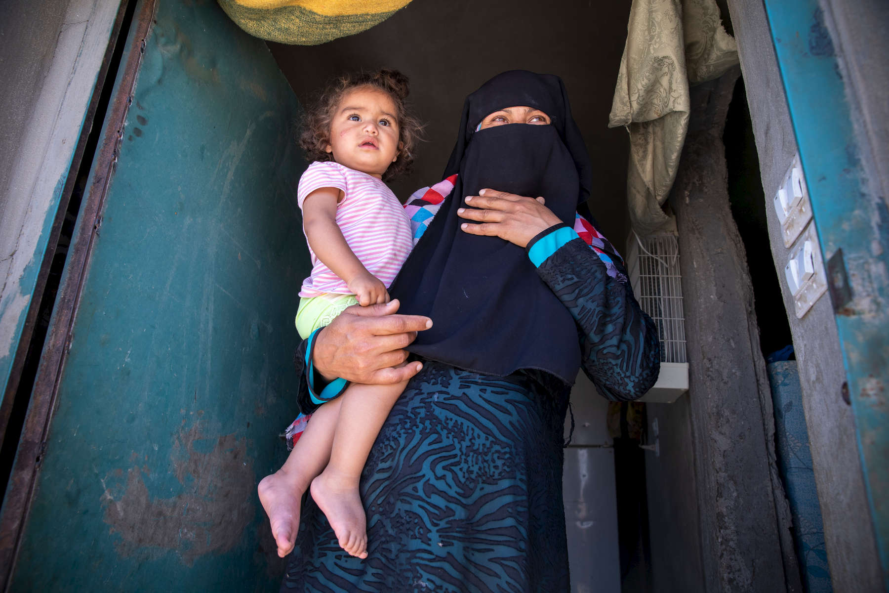 "Maha, 34, holds her 1-year-old daughter Heba. They are Syrian refugees. Maha's husband Mohammad has worked on and off in Jordan for several years, but the war in Syria has made it his permanent home—his house in Syria has been burned down. When his wife followed as war closed in, she was placed in Jordan's Azraq camp but fled after a few weeks. Together, they struggle to provide for their five children, who are out of school.Maha and Mohammad were separated by the war for more than two years. When they reunited, their daughter, Alala, didn't recognize him. Today they live together in a small tent in Jordanian desert, trying to scrape together work until peace returns.A few of Maha and Mohammad's kids are old enough to remember when war broke out in their town. ""My daughter, when the plane came … she started to cry, because she saw, in front of us, the plane carrying out massacres of innocent people,"" Maha says. In Syria, Mohammad and Maha were small farmers raising their kids in peace. But since war forced them from home, now they live as refugees, struggling to cope with what their family has been through. ""I swear that when the night comes, and we hear the sound of planes, my body starts to shake out of fear for my sons,"" Maha says.Mercy Corps connected the family to mobile banking, which they use to pay bills and save money on their phones. Their dream today is to continue on to Europe where their kids can continue their educations and live in peace. ""I've suffered,"" Mohammad says. ""I don't want them to suffer like me."""