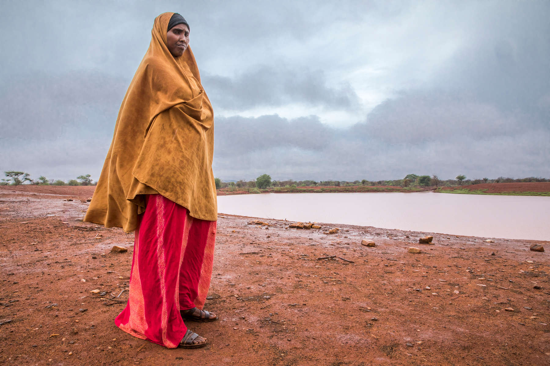 Kaltuma Sheikh Abdullahi, 30, stares out at a reclaimed reservoir in Anole, a small village about 85 km northeast of Wajir. Mercy Corps helped expand the reservoir so the community could get through the drought that has been punishing the region. Mercy Corps also helped to set up an system to control animal access to the water so to avoid disease and fouling of the water. With a pastoral economy based on herding livestock, Kaltuma and her neighbors feel every twitch of the climate, and lately, the rains have been all wrong. Previously the rains used to come twice a year: once at the beginning of the year and once at the end. Now the rains are less frequent and lighter. Sometimes it will be two years between rains, and although it had rained the night before Mercy Corps visited the village, turning the packed dirt roads to muddy rivers (the first rain since the end of November), it was only one day, and it's not enough to do much against a four-year drought. To help communities like Kaltuma's 30 adapt to climate change, Mercy Corps has conducted awareness campaigns on how to protect natural resources.