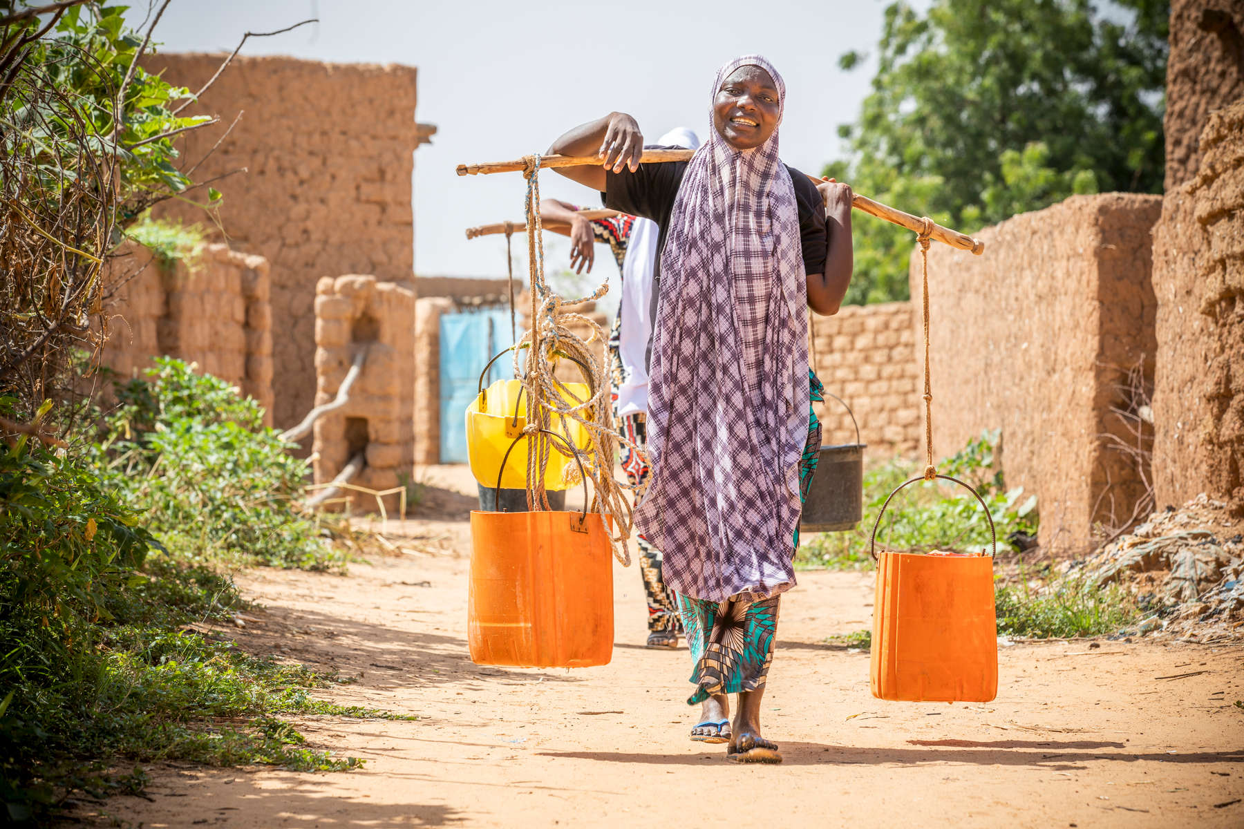 "Halima Issoufou, 26, collects water for her family. Halima lives with her husband and three children in a rudimentary mud hut in a rural village outside Niger's capital city, Niamey. Families here rely heavily on agriculture and nearly everyone lives hand-to-mouth. Halima's family is no exception, and her daily life is not unlike every other woman's in her village: from sunrise to sunset she works to care for the household, spending most of her time laboring over the day's next meal. Every day she cleans the home and dishes, collects water and firewood, and pounds millet to make the family's porridge, an arduous, lengthy process which she finishes just in time to start again. But all this work isn't enough, and the family often goes without eating — poverty is rife and they are not able to grow enough food to last them the year. ""In this area, people's lives are based on agriculture, which does not answer their needs because of the rain,"" Halima explains. ""People constantly face drought, and that makes people suffer a lot.""Between 2014 and 2016, Mercy Corps' ECOUT program responded, providing them with millet seeds; cash-for-work to restore farmland; goats; and training on agriculture, nutrition and hygiene. While conditions remain harsh and finding enough food is still a daily struggle, the family is still feeling some of the benefits from that program, particularly the hygiene and sanitation training, through which Halima learned to wash her dishes before cooking, and exclusively breastfeed her children for the first six months of life."