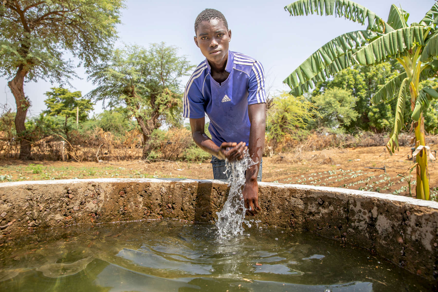 "Abdoulfataou Ganda, 18, stands next to a well on his farm. ""Most of our friends migrate to seek a better life,"" Abdoulfataou explains. He has taken over his father's farm, which earns him enough to be self-reliant and support his family. Like many youth in his community, he is at risk of migrating in search of opportunity, which means their communities are losing talent and skill to other places. But Abdoulfataou participated in Mercy Corps' financial literacy training, where he learned about budgeting, saving and how to seek microfinance support for business, which helped solidify is believe that a good life is possible at home. ""To me, it's always better to be at your home, that's where you can naturally be fine,"" he says. ""Home is home. And I believe that you can make a business and a good living even here, as long as you have something to do."" Driven by poverty, a lack of opportunity, and cultural expectation, many people in Niger migrate to different areas or countries for months or years at a time to earn income and experience life outside their home community. Migration routes have become increasingly dangerous and costly, putting migrants who don't know their rights at risk of violence or exploitation. However, migration also has the benefit of enabling people to gain skills they would otherwise not, which they can utilize in their home communities if they return and have access to opportunities. Mercy Corps' AMIPA program works with returning migrants and those at risk of migrating to provide education about the risks, so people can make informed decisions, while also providing financial inclusion and business support for those who have returned or choose to stay, so that they may access livelihoods in their home communities."