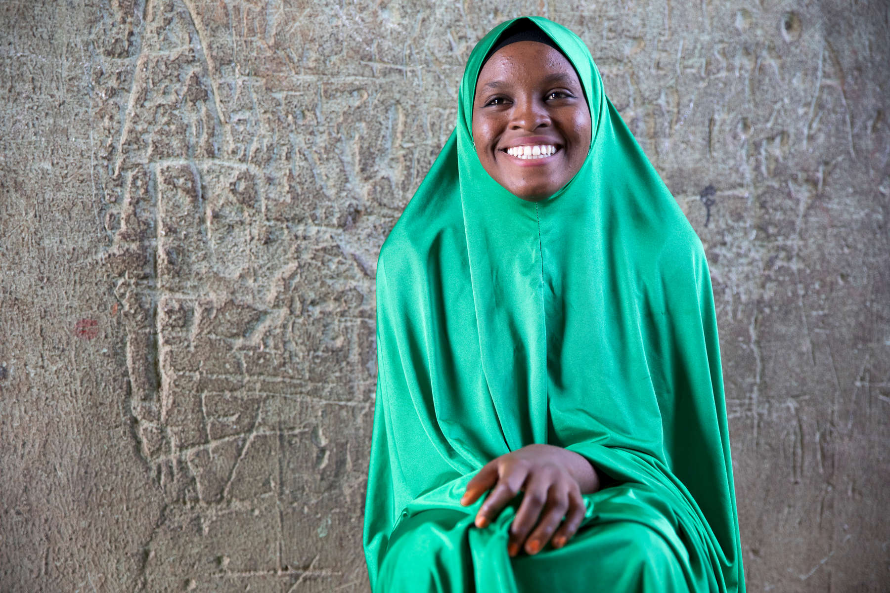 October 2018, Biu, Nigeria.  Fatima, 17, in her family's home. She started her own business selling sugar. She was motivated to start after learning about savings and money management in Mercy Corps' I-SING program, which provides safe spaces, livelihood grants and vocational training to vulnerable youth in Boko Haram affected communities in Nigeria.Now she sells in two locations — her home and her father's retail shop — and saves the income between a home bank and the Mercy Corps-facilitated savings group (VSLA) where she is a member. When the VSLA pays out next month, she is excited to build her business even more. Even though her family is struggling to meet their needs, Fatima is determined to finish school and be self-sufficient, believing independent women are the key to development. She wants to be a midwife when she is older, so she can help women more.
