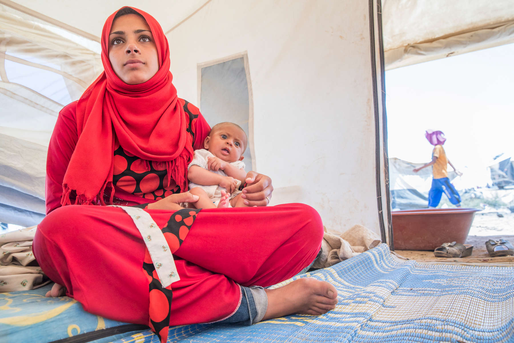 Marwa holds her 3 month-old daughter Farah, inside the tent where they are staying temporarily. She and her husband, Ali, fled the violence in their hometown and are now living in a displacement camp. Ali used to work selling vegetables out of his car, but there is no work in the camp. Mercy Corps is helping to meet the needs of families across Syria who are fleeing the violent conflict, providing them with basic essentials. This has included providing new arrival kits in this informal settlement.