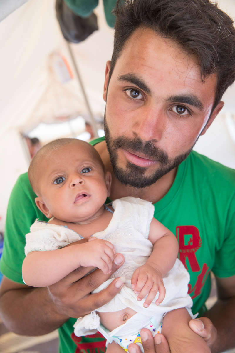 Ali holds his 3 month-old daughter Farah, inside the tent where they are staying temporarily. She and her husband, Ali, fled the violence in their hometown and are now living in a displacement camp. Ali used to work selling vegetables out of his car, but there is no work in the camp. Mercy Corps is helping to meet the needs of families across Syria who are fleeing the violent conflict, providing them with basic essentials. This has included providing new arrival kits in this informal settlement.