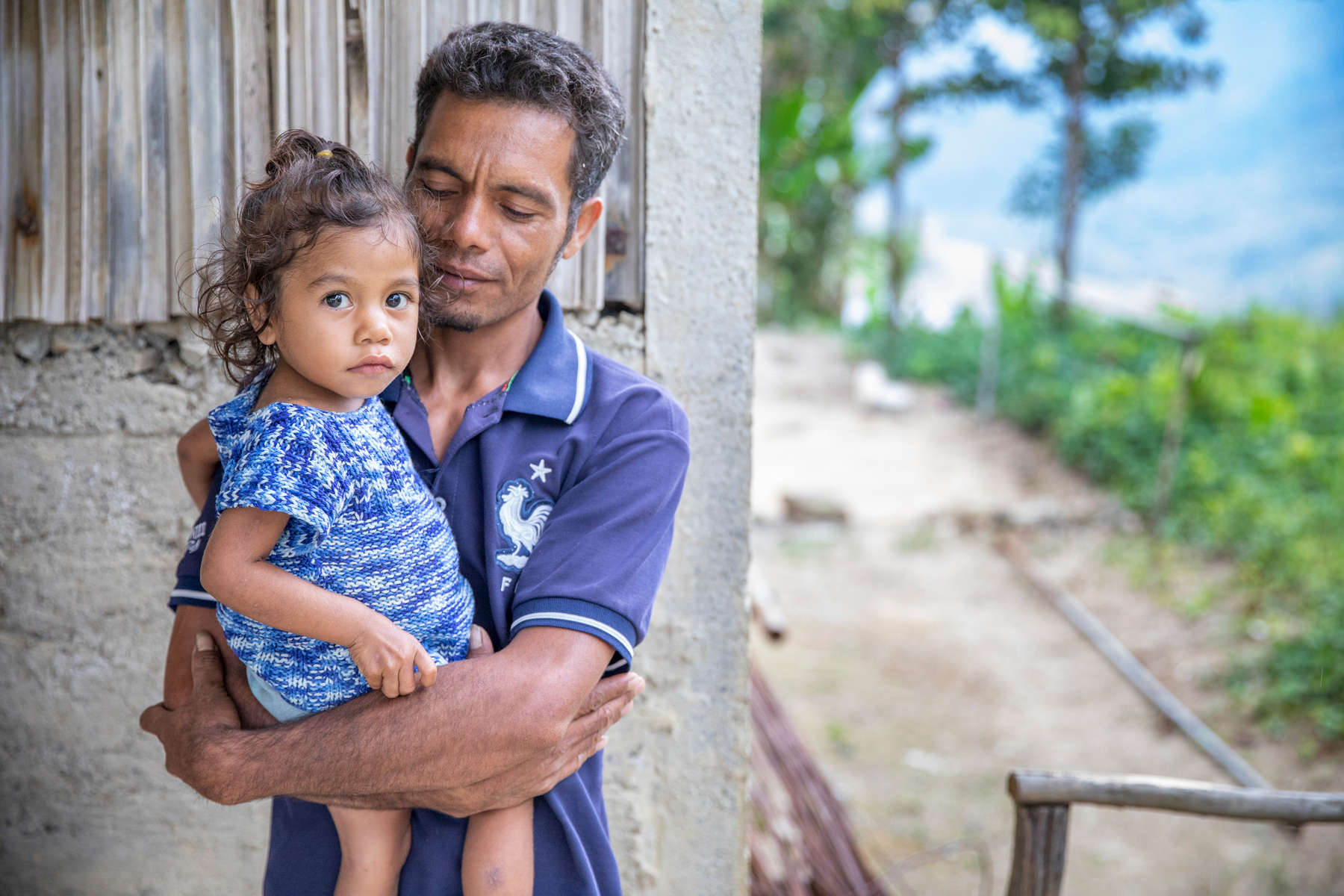 """Romeo, 28, holds his daughter Maria, 2. His niece Lourdes is a 19-year-old girl whose dream is to become the Minister of Education. For four years now, she's been using a solar lantern provided by Mercy Corps to study at night, after completing her daily chores.When asked if she had any advice or words of encouragement to share with other, younger Timorese girls who are chasing their own dreams, Lourdes said {quote}Being young, a girl, is something to be grateful for. Take the opportunity to chase your dreams — while your parents are still here, while they're still able to educate you and send you to school. Go to school, and take advantage of any opportunity to focus on your dreams. Don't think about something else. Most girls in Timor marry young. Please, don't get married young. Finish your education, find a job, and help your parents, give back to your parents for helping educate you."""""""