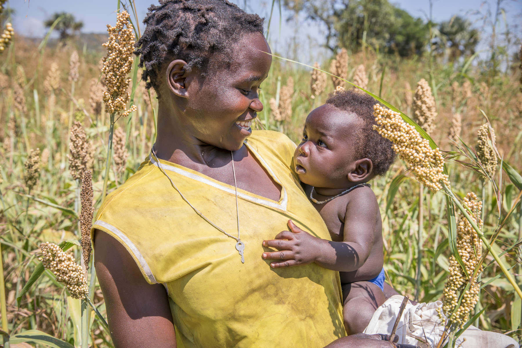 Bayoa Dominica, 24, and her 7 month-old son Good Lucky Haron stand in a field of white sorghum. Bayou is a member of a Mercy Corps supported farmers group, composed of both host community Ugandans and South Sudanese refugee men and women, who work together for better crop production. South Sudanese refugees are given small plots of land, and Ugandan nationals have larger plots but very few people to work the land. Together they combine their resources and labor. Mercy Corps provided each farmer with a voucher for 20,000 Ugandan shillings, and many of the farmers groups pooled their vouchers together to buy greater quantities of seeds and more products. Mercy Corps also organized a trade fair between the farmers and the agro dealers so that they could spend their vouchers and purchase what they needed. Caroline Mandera is a Ugandan widow with 7 children, and has been part of the group for 3 months. She says {quote}I joined the group because in the group we have savings. I use the money from the group to pay school fees. I also join hands with the farmers to produce some of our products. We pick and then we sell them.{quote}  Mercy Corps will also be supporting these farmers groups to establish VSLAs (Village Savings and Loans Associations) so that members will be able to begin to save some of the money they earn through the sale of crops.
