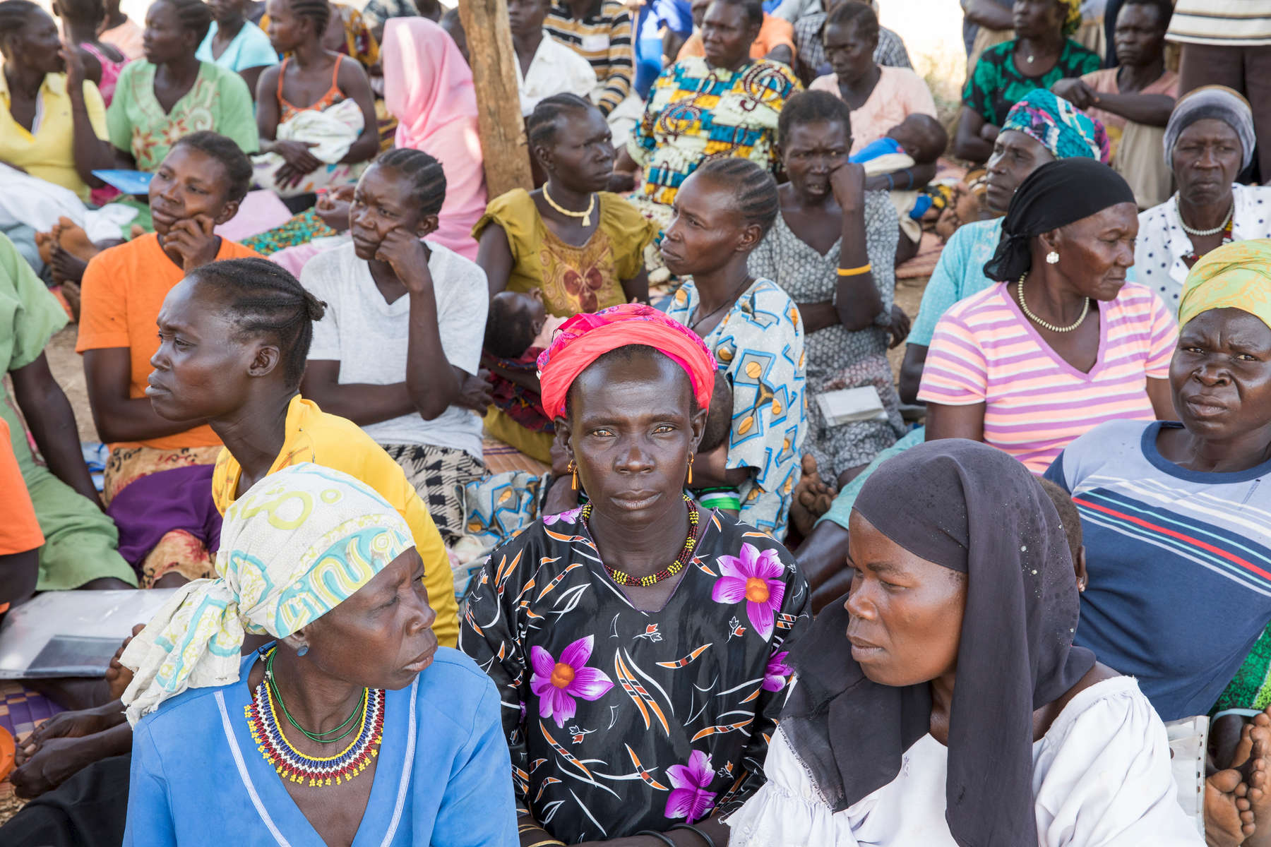 Apate Amina, 37, waits in line at a Mercy Corps cash distribution. She comes from Kimba, in the Central Equatoria region of South Sudan, and arrived in Bidi Bidi in October 2016. Apate takes care of 12 children, 7 of her own and 7 that belonged to her sister who was killed by stray bullets during the recent conflict. She received a payment of 84,0000 Ugandan shillings from Mercy Corps in December, and will receive another payment in March 2018. All of the refugees who received the cash distribution are members of Mercy Corps-supported farmers groups. The objective of the cash distributions are to help them delay the sales of their harvests, so they can sell their produce at higher prices. If they can delay long enough, they don't have to eat or sell their seeds before the next planting season.