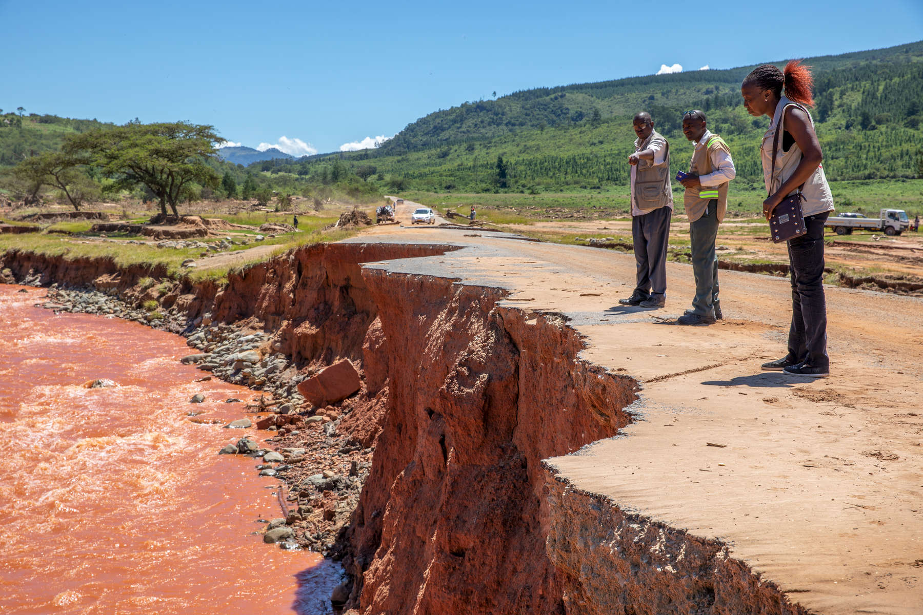 Mercy Corps WASH Specialist Vimbayi Mazanhi (right) peers over the edge of a damaged bridge over the Nyahodi river, which burst its banks and washed away an entire market full of stalls, vendors and customers. It is estimated that 14 bridges around Chimanimani were destroyed, paralyzing transportation and making aid delivery slow and treacherous.