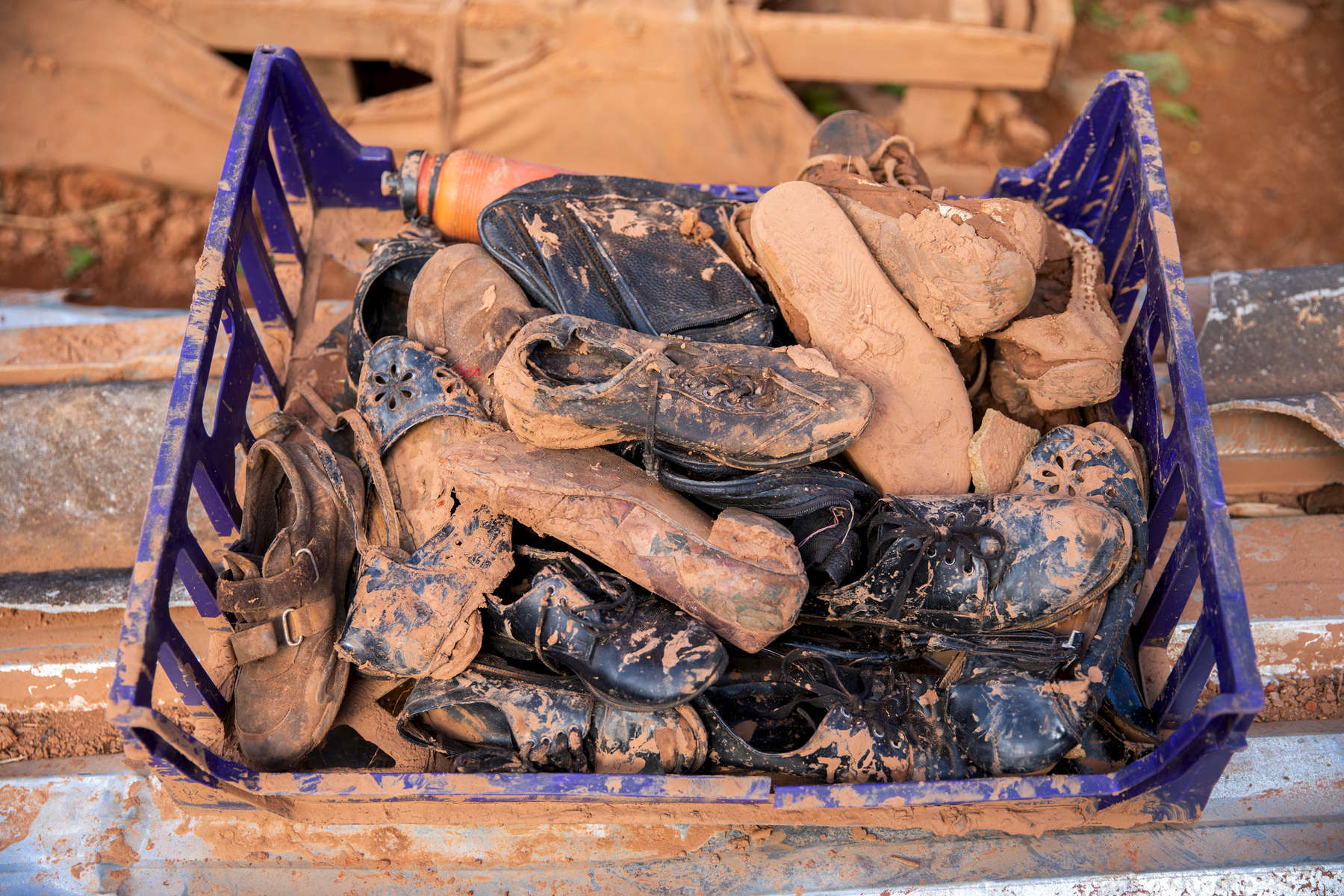 A box of muddy shoes that Anthony Machingauta, 52, recovered from his home.