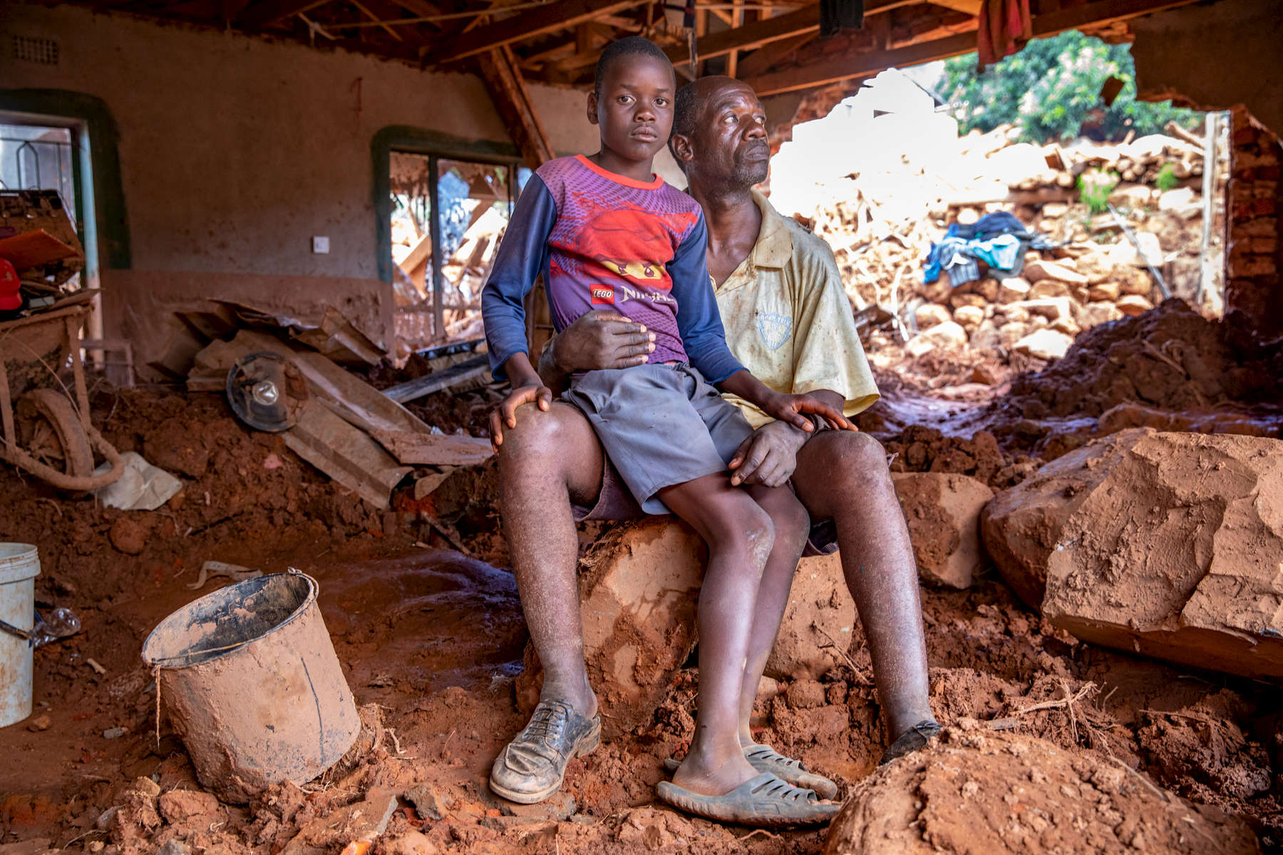 Anthony Machingauta, 52, is a schoolteacher. His son Leonard, 15, sits on his lap in the middle of their home. On March 16th, rains from Cyclone Idai unleashed mudslides from the hills surrounding Ngangu, which crushed the front wall of their house and exited out a side wall, leaving 4 feet of mud and unmovable boulders throughout their home. Anthony and his three sons all survived, but he is concerned about how he will be able to afford to feed them and pay their school fees.