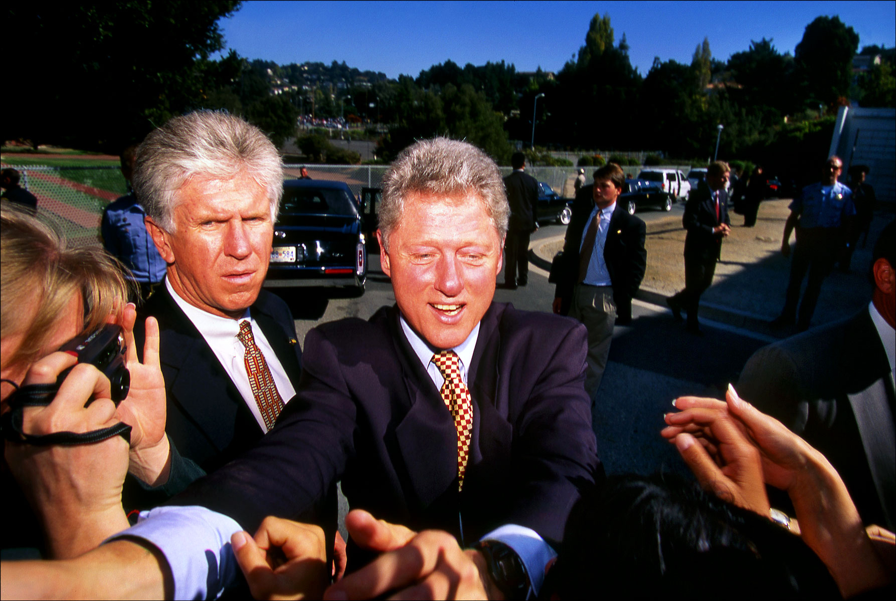 Photo of President Clinton (while he was President), flanked by Secret Service Agents as he greets bystanders near San Francisco. (for Business Week magazine)