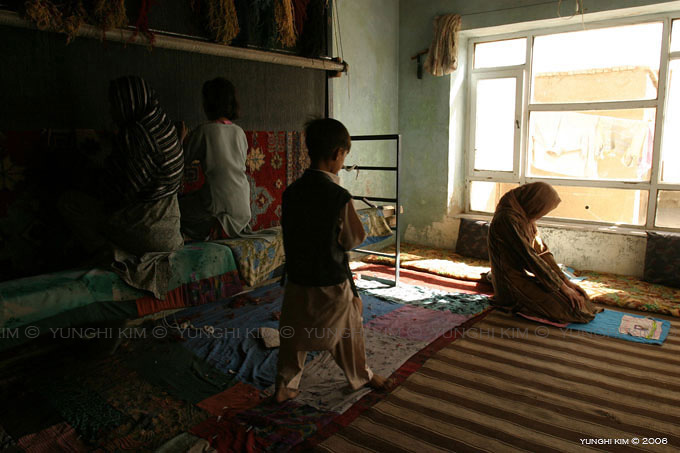 Miriam and her 5 children make a living by weaving rugs in their one room rental 16 hours a day.  Only one daughter attends school.  On right, eldest daughter Nasiba, 16, prays during Ramadan.