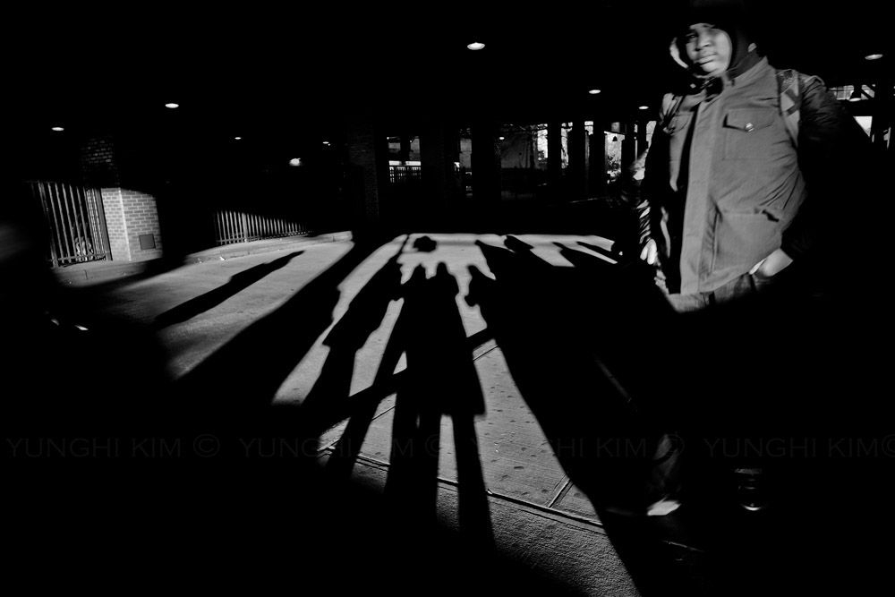 Shadows cast commuters rushing past at a busy Stillwell Subway Station.  Yunghi Kim ©2014.
