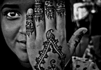 9/23/15 NY Neighborhood series. Jackson Heights Queens. A woman gets her hand painted with henna night before the Eid . (she didnt want to give her name).  74 street is filled with henna stands by teens making few extra dollar. © 2015 Yunghi Kim/Contact Press Images.