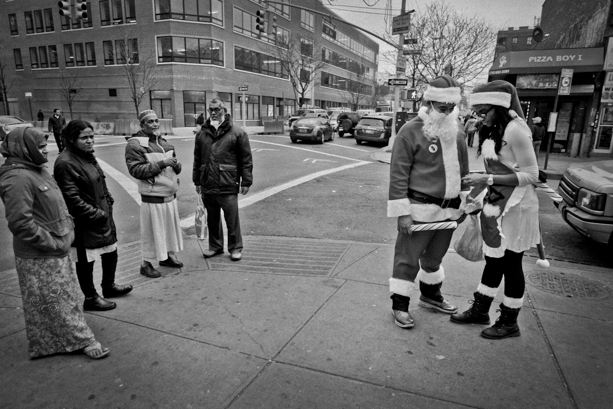 12,11,2015 NY Neighborhood profiles series.  Jackson Heights Queens.  Two dressed for SantaCon passed through 74 th Street. © 2015 Yunghi Kim/Contact Press Images.