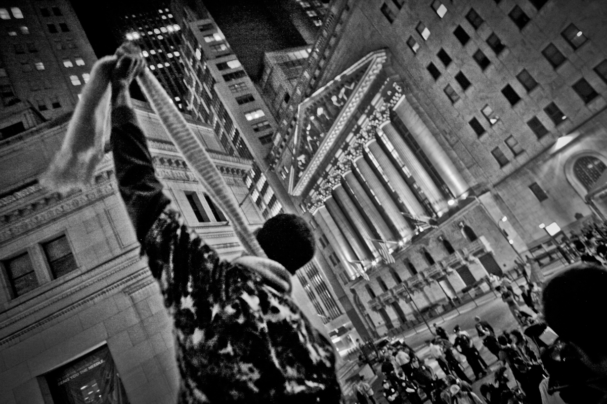 With the iconic NY Stock Exchange as a backdrop, a protester motions death to Wall Street NYC 2012. ©2017 Yunghi Kim/ Contact Press Images