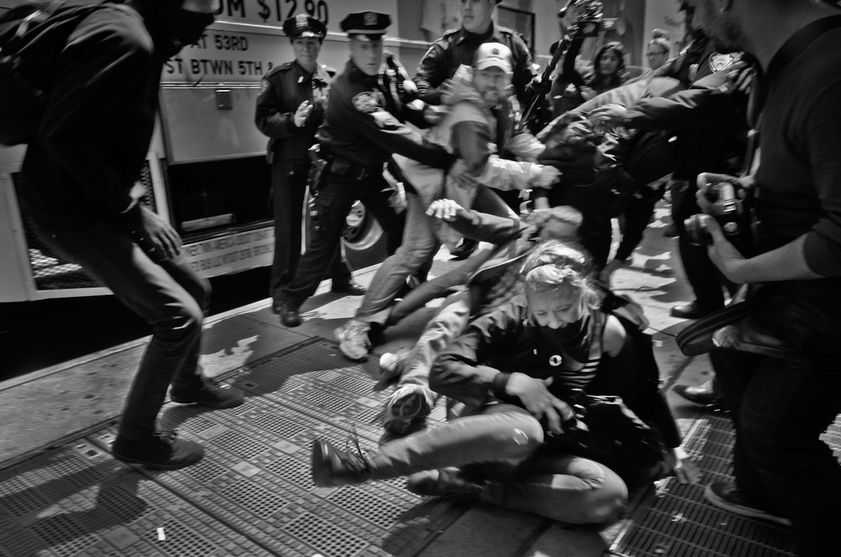 At the May Day Protest, NYC 2012. Undercover and uniformed NYPD scrambles to nab a Black Bloc protester, as others try to rescue her from NYPD's grip. ©2017 Yunghi Kim/ Contact Press Images