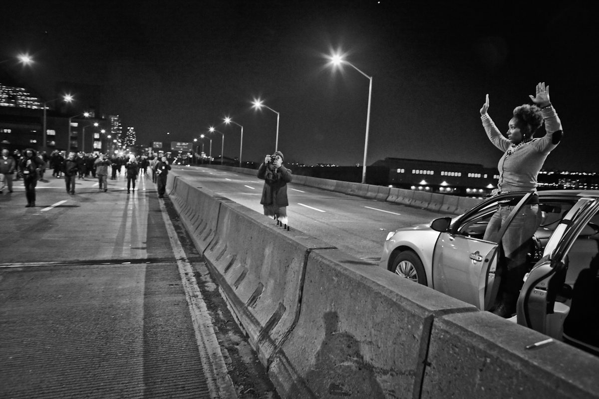 Busy West Side Highway, a woman gets out of her car and show support with protesters by gesturing {quote}hand up, dont shoot.{quote}  Protests erupted nationally for days when a grand jury declined to indict NYPD Police Officer Daniel Pantaleo who used chokehold in the death of Eric Garner in July 2014. Dec 2014. ©2017 Yunghi Kim/ Contact Press Images