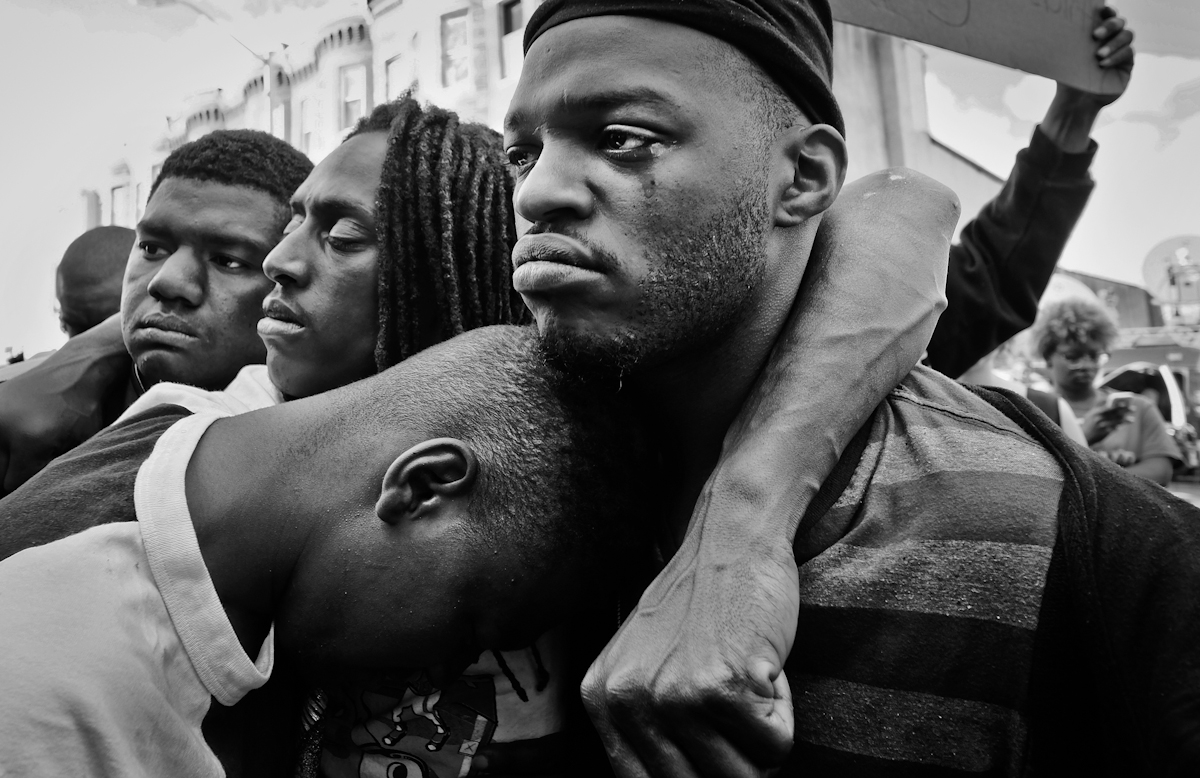 BALTIMORE, MD - APRIL 28, 2015 Men mourn the death of Freddie Gray at a protest in West Baltimore.  Gray died from spinal cord injury sustained while in police custody. String police shootings and brutality have launched national protests with high profile deaths of Michael Brown in Ferguson, Missouri, Eric Garner in New York and Freddie Gray in Baltimore and others. With Baltimore and Ferguson riots, the country continues to struggle with the realization the race relations in America have not changed much and many compared it to the struggles before of the Civil Right Movement era of 1960's. ©2017 Yunghi Kim/ Contact Press Images