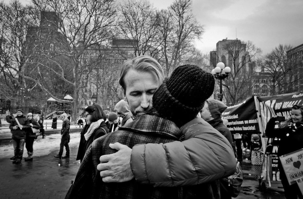 At an mmigration protest, Washington Square Park, NYC 2017, a couple in the chaos of a protest and street musicians. ©2017 Yunghi Kim/ Contact Press Images