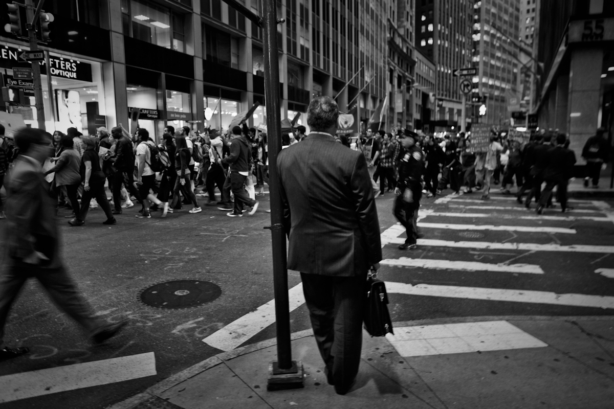 Man in a suit waits as the Occupy Wall Street protest passes on Wall Street. Protesters would march daily through side streets around Wall Street shouting {quote}Banks got bailed out and we got sold out{quote}  ©2017 Yunghi Kim/ Contact Press Images