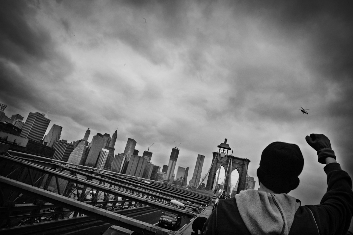 Occupy Wall Street  protesters  march across the Brooklyn Bridge NY under the watchful eye of NYPD helicopter. April 1, 2012. ©Yunghi Kim. ©2017 Yunghi Kim/ Contact Press Images