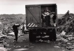 A man tries out a  guitar in a truck filled with looted goods, Mugungu refugee camp.
