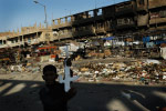 A boy brandishes a toy kalashnikov on a main thoroughfare food market the day after it was heavily damaged forces and the Mahdi Army. U.S. forces blasted the apartment from helicopter gunships.