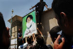 Demonstrators hang a picture of Muqtada al-Sadr's uncle, Mohammed Bakr al-Sadr, a Shiite cleric who was assassinated for opposing Saddam Hussein, on a wall outside the green zone. The protest was in response to U.S. military actions against Muqtada al-Sadr and the Mahdi Army. Thousands of al-Sadr's supporters participated, including some Iraqi police.