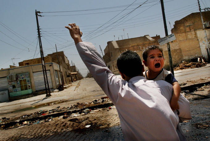 A father shows his hand to snipers as he carries his terrified child across the front line between U.S. forces and the Mahdi Army at the wrecked outskirts of the old city.