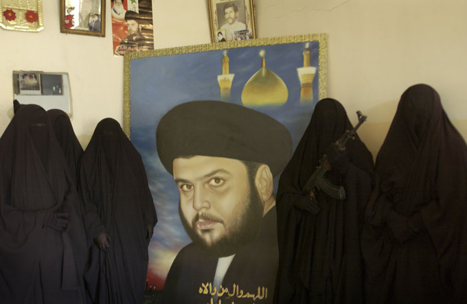 Followers of Muqtada al-Sadr pose with a portrait of their leader. The women assist the Mahdi Army by supplying the fighters with food and other support during battles with U.S. forces. They say they are willing to fight for the militia if the need arises.