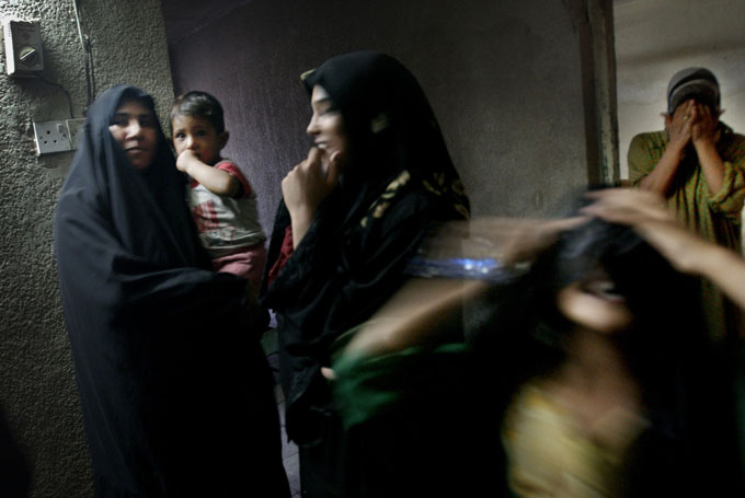 Women friends gather at home while their husbands meet in Sadr City, a stronghold of the conservative Shiite leader Muqtada al-Sadr and his armed followers, the Mahdi Army.