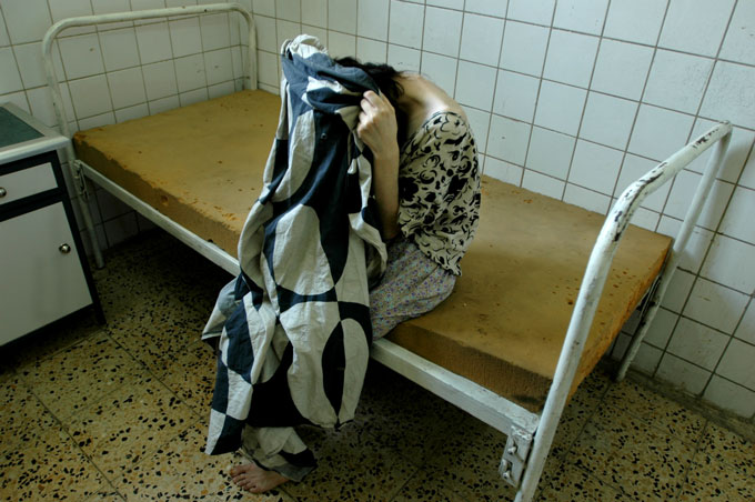 """A patient at the Rashad Psychiatric Hospital weeps inconsolably. The nurse said, """"She is suffering from a broken heart."""""""